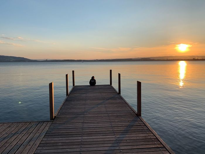 Water Sunset Beauty In Nature Pier Sky Tranquility Scenics - Nature Tranquil Scene One Person Idyllic Sea Real People Jetty Leisure Activity Lifestyles Nature Rear View Wood - Material Outdoors Horizon Over Water
