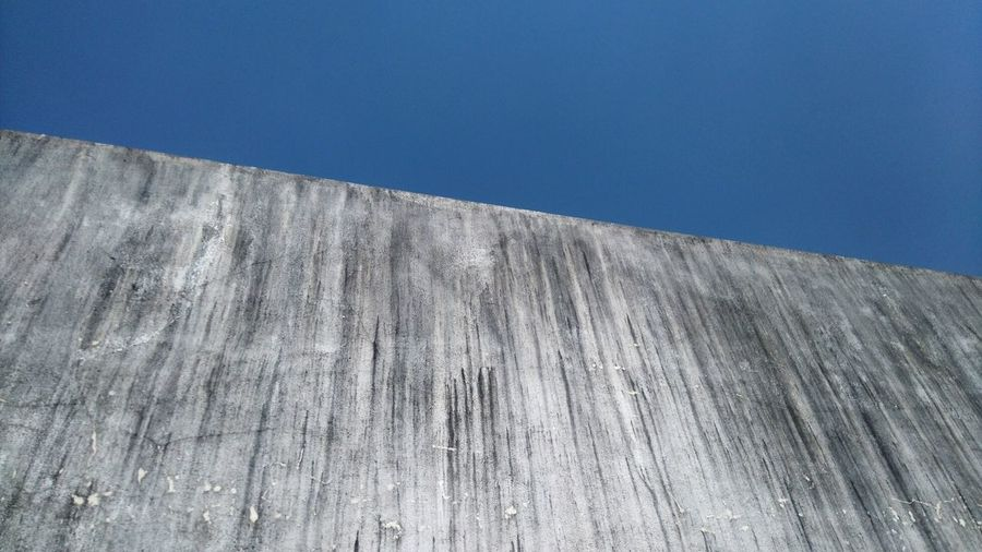 Low Angle View Of Old Concrete Wall Against Clear Blue Sky
