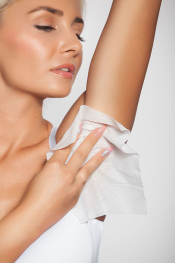 Young woman cleaning armpit with tissue paper against white background