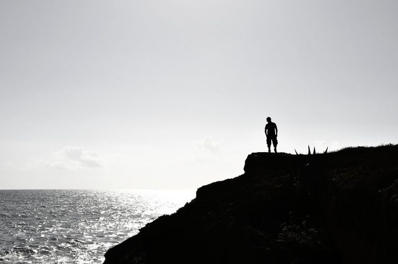 Silhouette man standing on rock by sea against sky