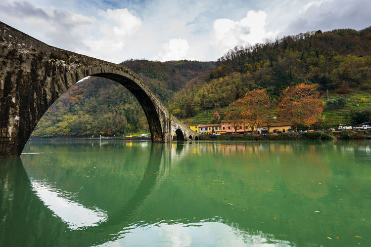 Devil's bridge in Tuscany in Autumn. Autumn Tuscany Arch Architecture Autumn Colours Beauty In Nature Borgo A Mozzano Bridge - Man Made Structure Built Structure Cloud - Sky Connection Day Nature No People Old Outdoors Reflection River Scenics Sky Tranquility Tree Water Waterfront