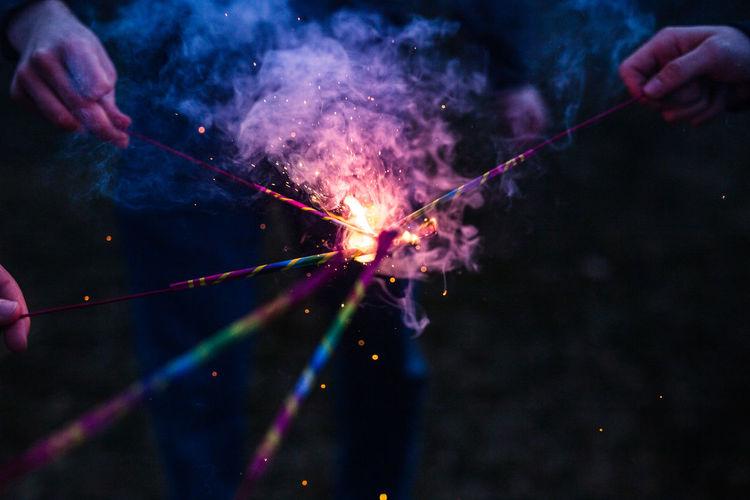 Cropped hands burning sparklers