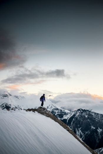 Man walking on snowcapped mountain against sky