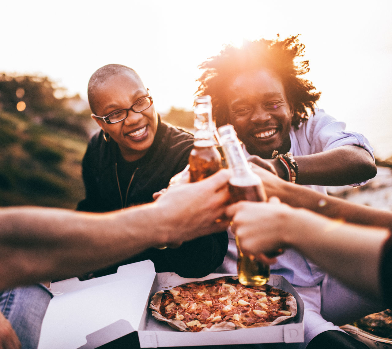 Friends toasting beer bottles while sitting against clear sky during sunset