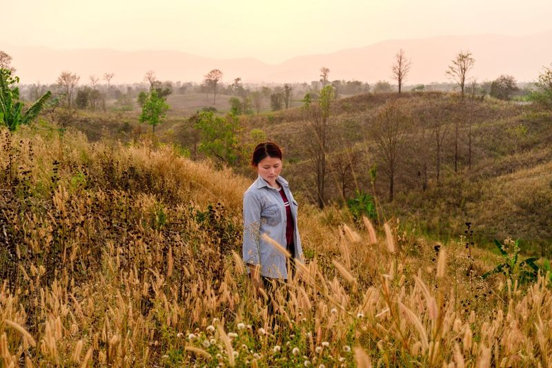 Sunset Flowering Plant Grass Traveling Relaxing Plant Land Real People Field One Person Growth Leisure Activity Lifestyles Sky Nature Standing Front View Landscape Beauty In Nature Women Outdoors