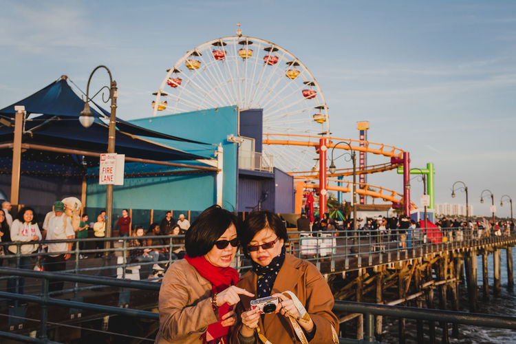 Two asian women look at photos they've taken while walking on Santa Monica Pier in California - IG: @LostBoyMemoirs Streetwise Photography Streetphotography Street Photography People People Watching people and places Amusement Park Ride Leisure Activity Real People Amusement Park Women Togetherness Ferris Wheel Lifestyles Santa Monica California The Art Of Street Photography