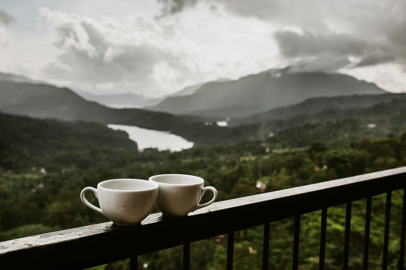 Coffee cup on railing against mountains