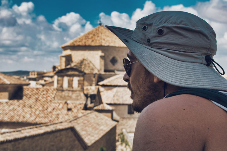 Side view of man wearing sunglasses and hat against houses