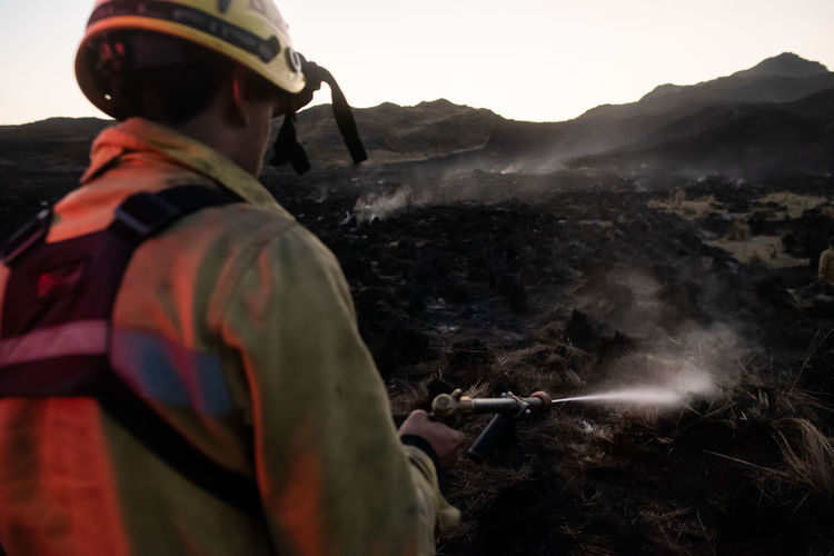 Rear view of firefighter extinguishing fire on mountain