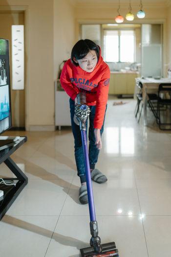 Full length portrait of girl standing on tiled floor at home