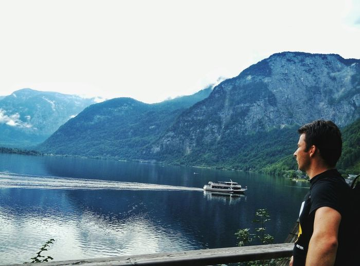 Side view of man looking at lake against mountains