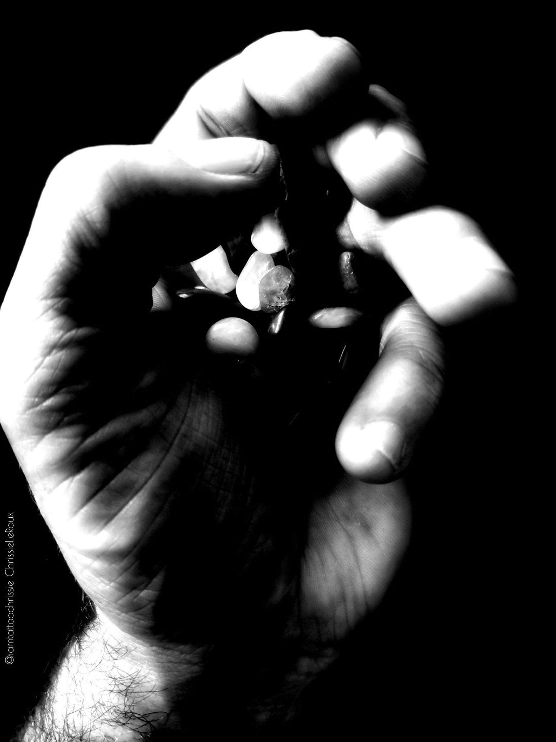 one person, hand, human hand, human body part, close-up, real people, indoors, black background, holding, unrecognizable person, body part, studio shot, sign, lifestyles, social issues, human finger, bad habit, finger, human face
