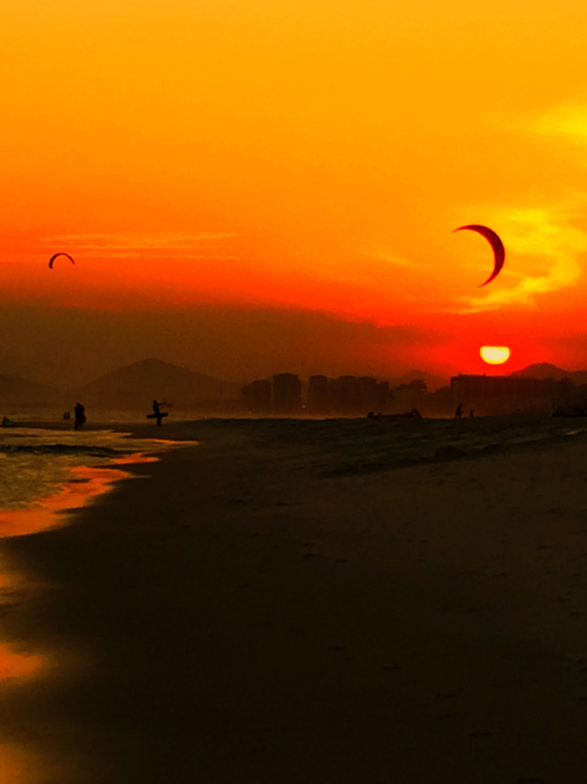 sunset, tranquil scene, scenics, tranquility, orange color, sun, beauty in nature, silhouette, idyllic, mid-air, mountain, nature, flying, sky, water, non-urban scene, moody sky, outdoors, majestic, enjoyment, romantic sky, dramatic sky, atmosphere, dark, paragliding, vacations