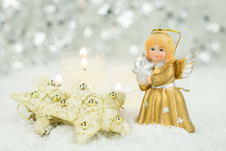 Festive Still Life of Golden Angel Figurine Next to Gold Stars on Snowy Surface with Burning Candles in Background with Copy Space Angel Art And Craft Celebration Childhood Christmas Close-up Creativity Decoration Female Likeness Figurine  Focus On Foreground Gold Colored Human Representation Indoors  Innocence Representation Snow Still Life Toy