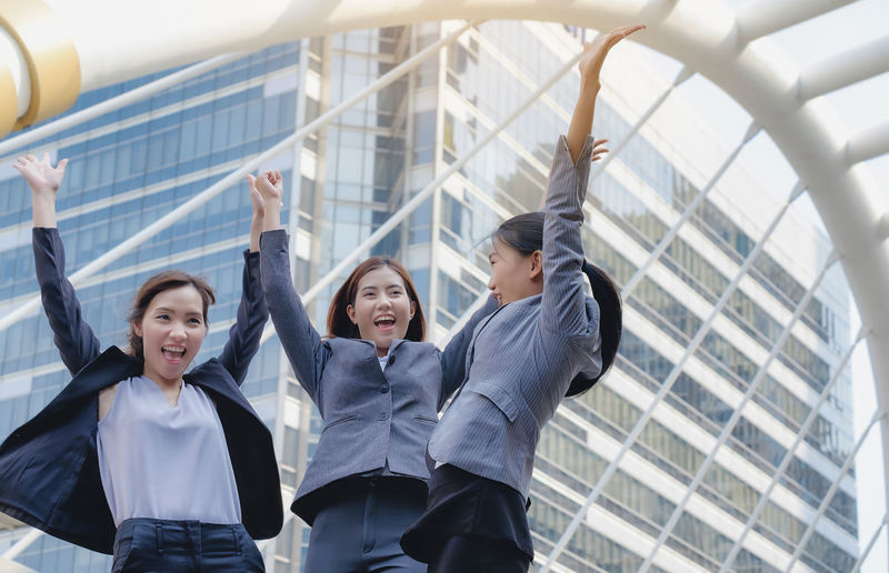 The group of business women is holding hands with great success. Architecture Arms Raised Built Structure Businessman Cheerful City Day Friendship Happiness Lifestyles Low Angle View Outdoors People Real People Smiling Teamwork Togetherness Women Young Adult Young Women