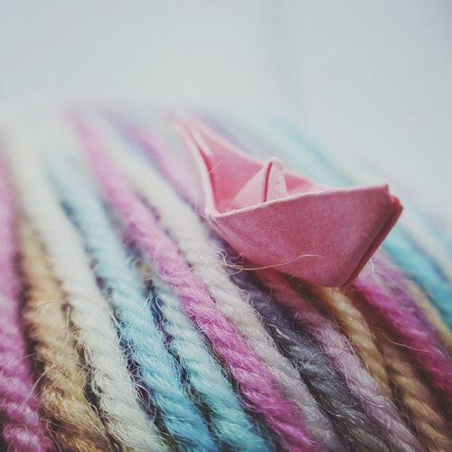 Close-up of paper boat on colorful wool