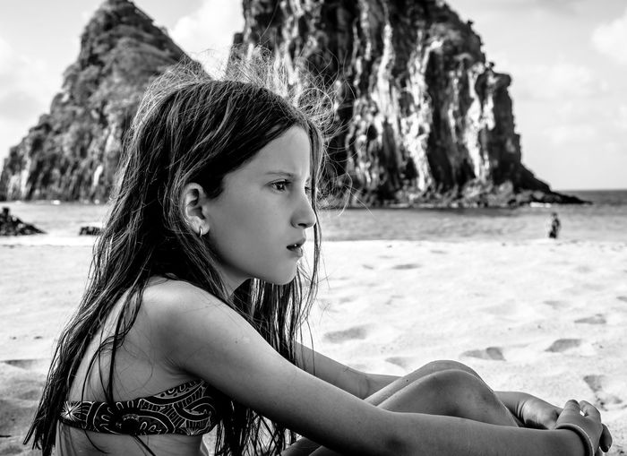 Side view of cute girl sitting at sandy beach