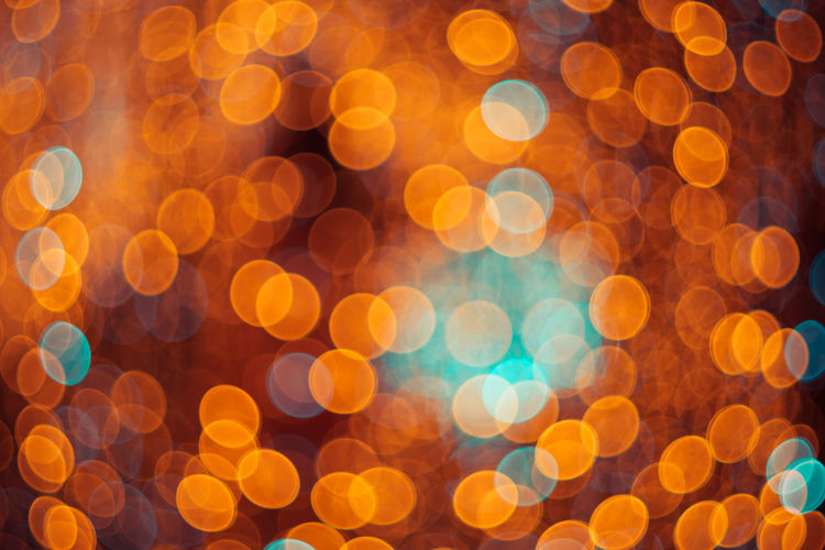Defocused Image Of Illuminated Christmas Lights At Night