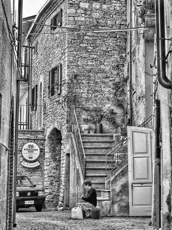 An old woman out of the door of her home peel of some vegetables Architecture Brick Wall Building Building Exterior Built Structure City Day Home Is Where The Art Is Italy No People Old Buildings Old Habits Old Ruin Outdoors Parked Residential Building Residential Structure Traditions Hidden Gems  People And Places