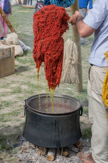 Natural wool dyeing in pots for carpet making Coloring Natural Paint Day Dye Freshness Human Hand Low Section Men Occupation One Person Organic Paint Outdoors People Real People Rug Standing Working