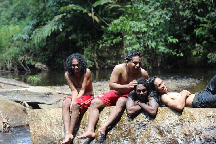 Happy men on rock in forest