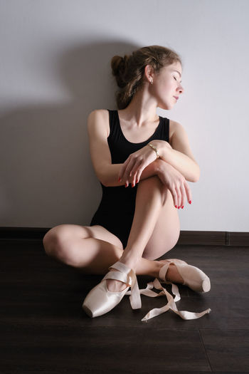 Full length of young woman sitting on floor