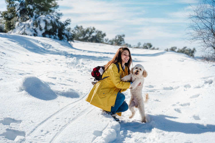 Woman with dog on snow during winter
