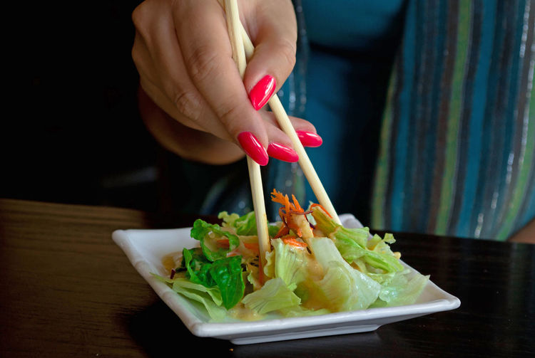 Cropped hand of woman having salad at table