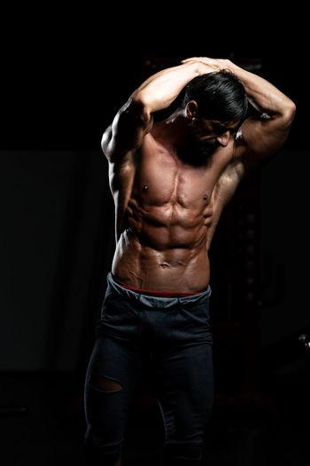 Close-up of shirtless man looking at camera