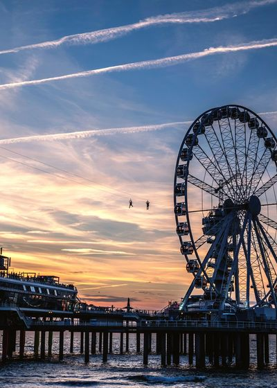Ferris wheel by river against sky during sunset