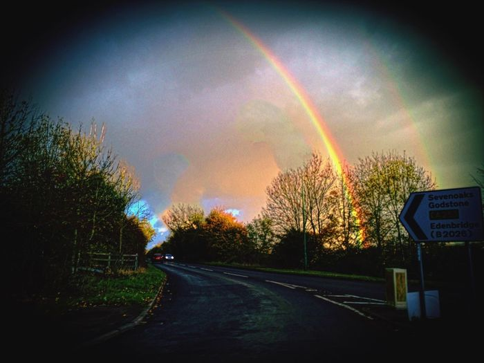 Maybe the signpost is a clue to the end of the rainbow? Rainbow Double Rainbow Road Tree No People Sky The Way Forward Beauty In Nature Cloud Formation Multi Colored See The World Through My Eyes Eyeem Market EyeEmBestPics EyeEm Best Shots EyeEmNewHere Beauty In Nature Taken From A Moving Vehicle Bushes Car Headlight Exceptional Photographs