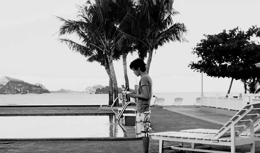 Teenage Boy Flying Drone By Poolside Against Clear Sky