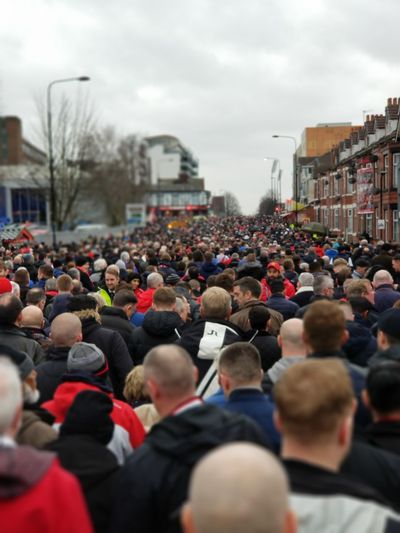 Crowd in city against sky