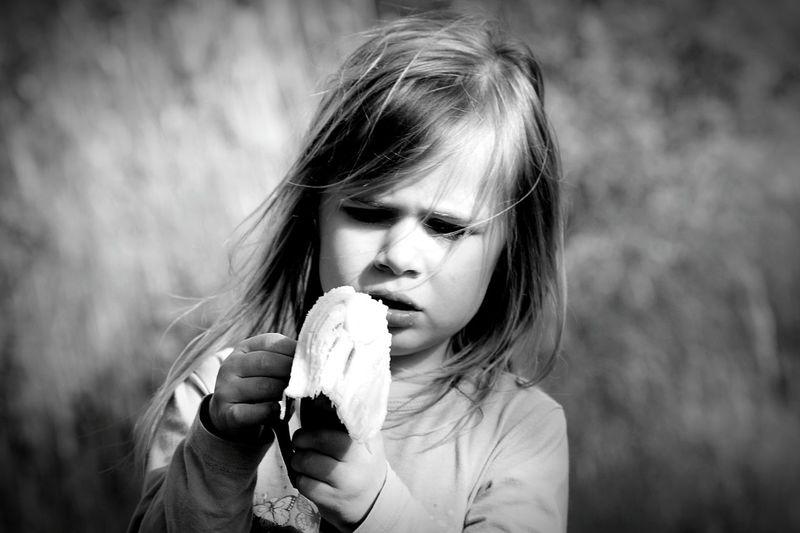 Close-up of girl eating banana at field