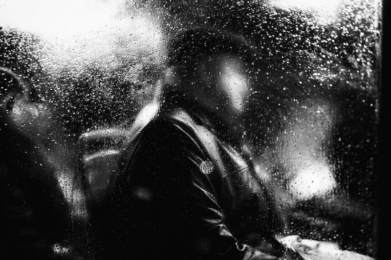 Man In Train Seen Through Wet Window During Rainy Season At Night