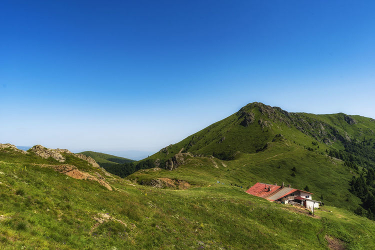 Idyllic landscape in the Old mountain, Central Balkan national park in Bulgaria. Eho hut surrounded with fresh green mountain pastures with blooming flowers in beautiful morning light at sunrise Sky Scenics - Nature Blue Beauty In Nature Mountain Copy Space Green Color Landscape Tranquil Scene Nature Environment Plant Land Clear Sky Tranquility No People Grass Day Non-urban Scene Idyllic Outdoors Bulgaria Central Balkan Balkan National Park Summer Sunset Sunrise Hut Echo Meadow Hot Warm Clothing Nature Old Clear Sky Trekking Hiking Tourism Vacation Weekend Reserve Scenary