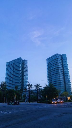 City street by modern buildings against blue sky