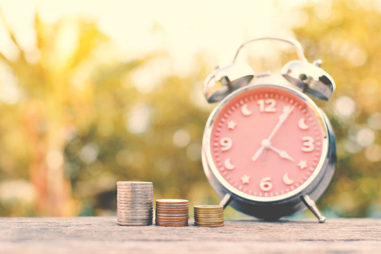 Close-up of coins stacked with alarm clock on retaining wall