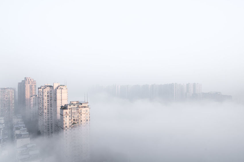 City emerging from dense fog or haze in the morning in China Fog Building Exterior Sky City Cityscape Copy Space Haze Smog Buildings Pullution Mysterious Beauty In Nature Morning Foggy Morning