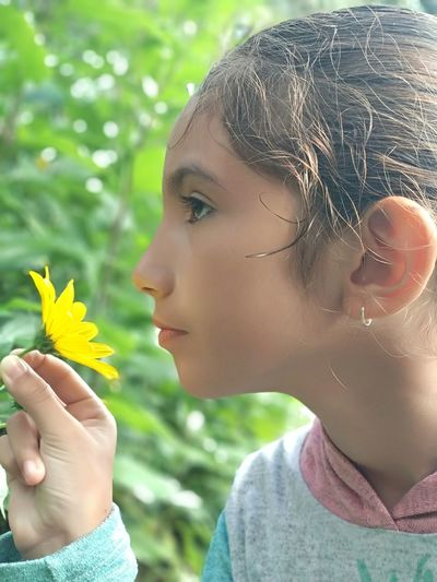 Close-Up Side View Of Girl Holding Yellow Flower