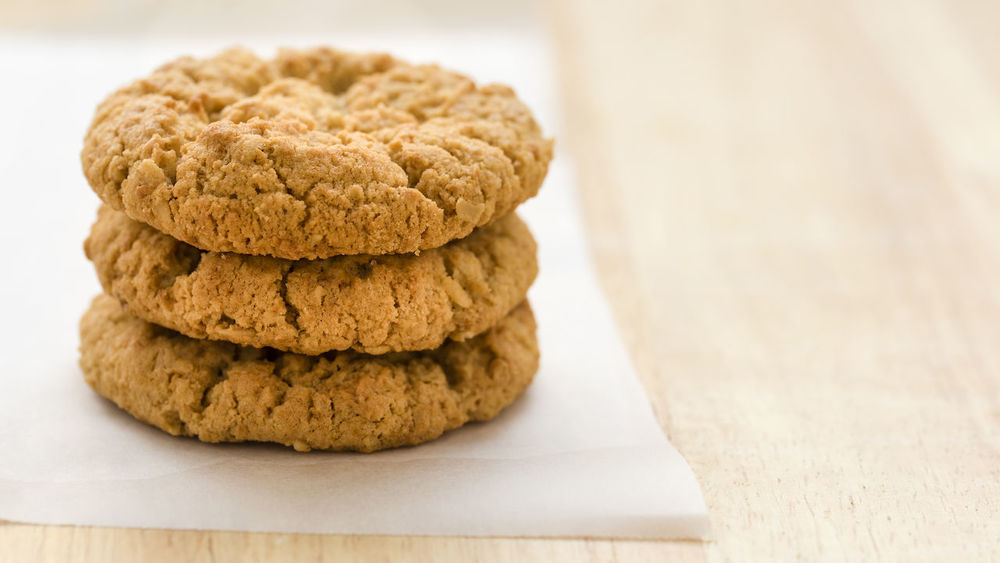 Stack of three golden ANZAC biscuits on baking paper Anzac Biscuits Cookies Golden Stack Backlit Baking Paper Close-up Cookie Crisp Food Freshness Indoors  No People Paper Ready-to-eat Round Snack Sweet Sweet Food Three
