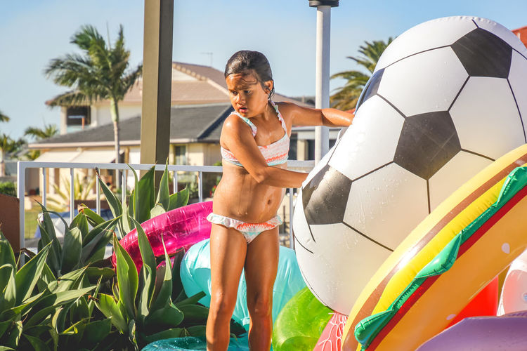young girl standing poolside holding a large soccer ball inflatable One Person Swimwear Leisure Activity Real People Three Quarter Length Shirtless Bikini Standing Tropical Climate Lifestyles Pool Nature Plant Day Clothing Palm Tree Multi Colored Swimming Pool Outdoors Inflatable  Girls Childhood Diversity Summertime
