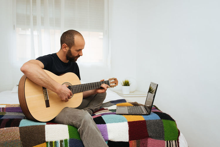 Man playing guitar while looking at laptop