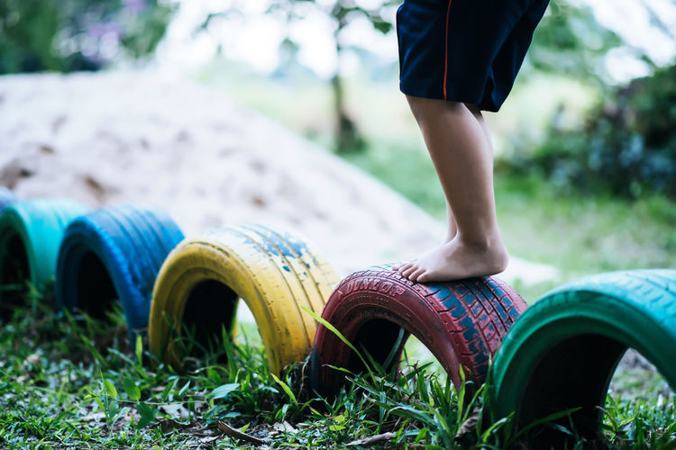 Low section of boy standing on tires at playground