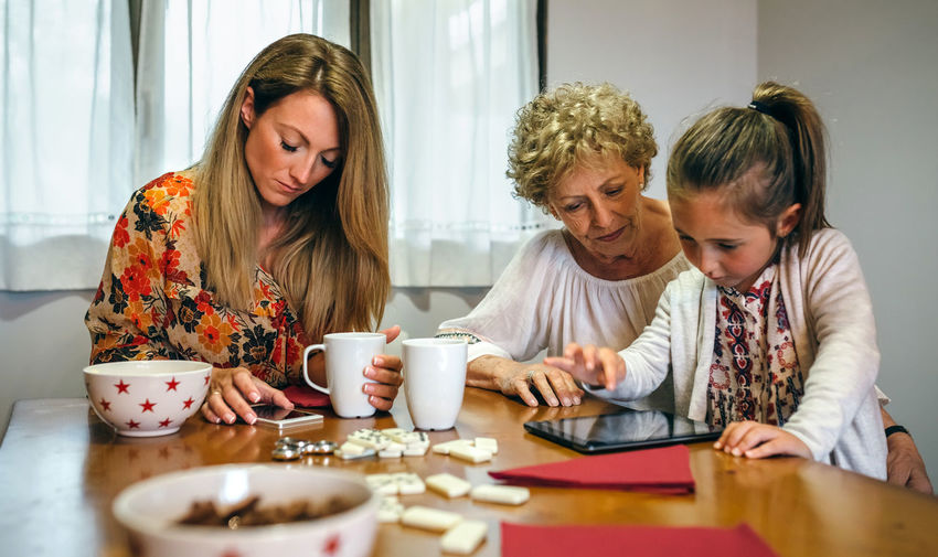 Girl with mother and grandmother using digital tablet on table at home