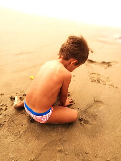 Rear view of shirtless boy playing with sand at beach