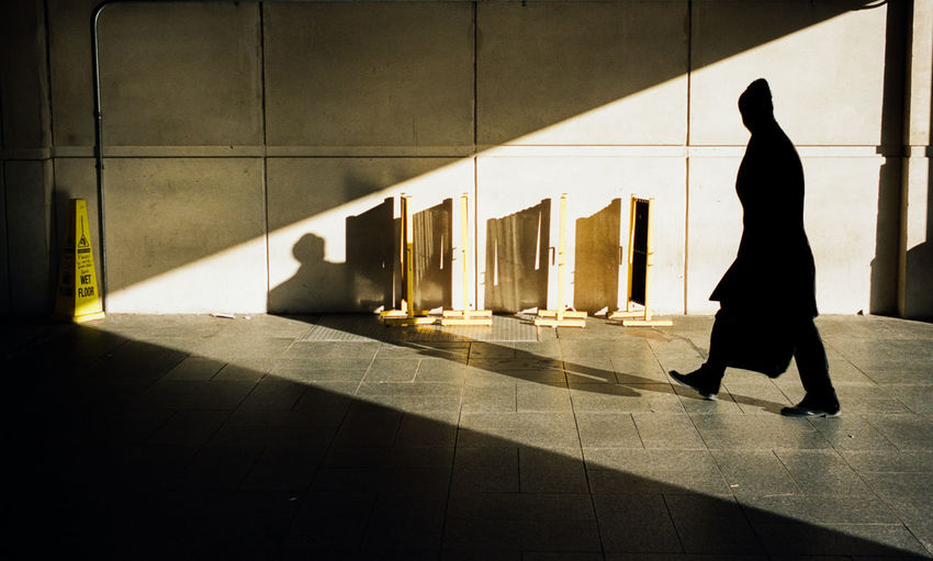 Shadow of woman walking on tiled floor in building