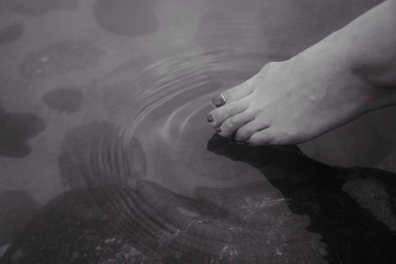 Leg Of Woman Touching Water