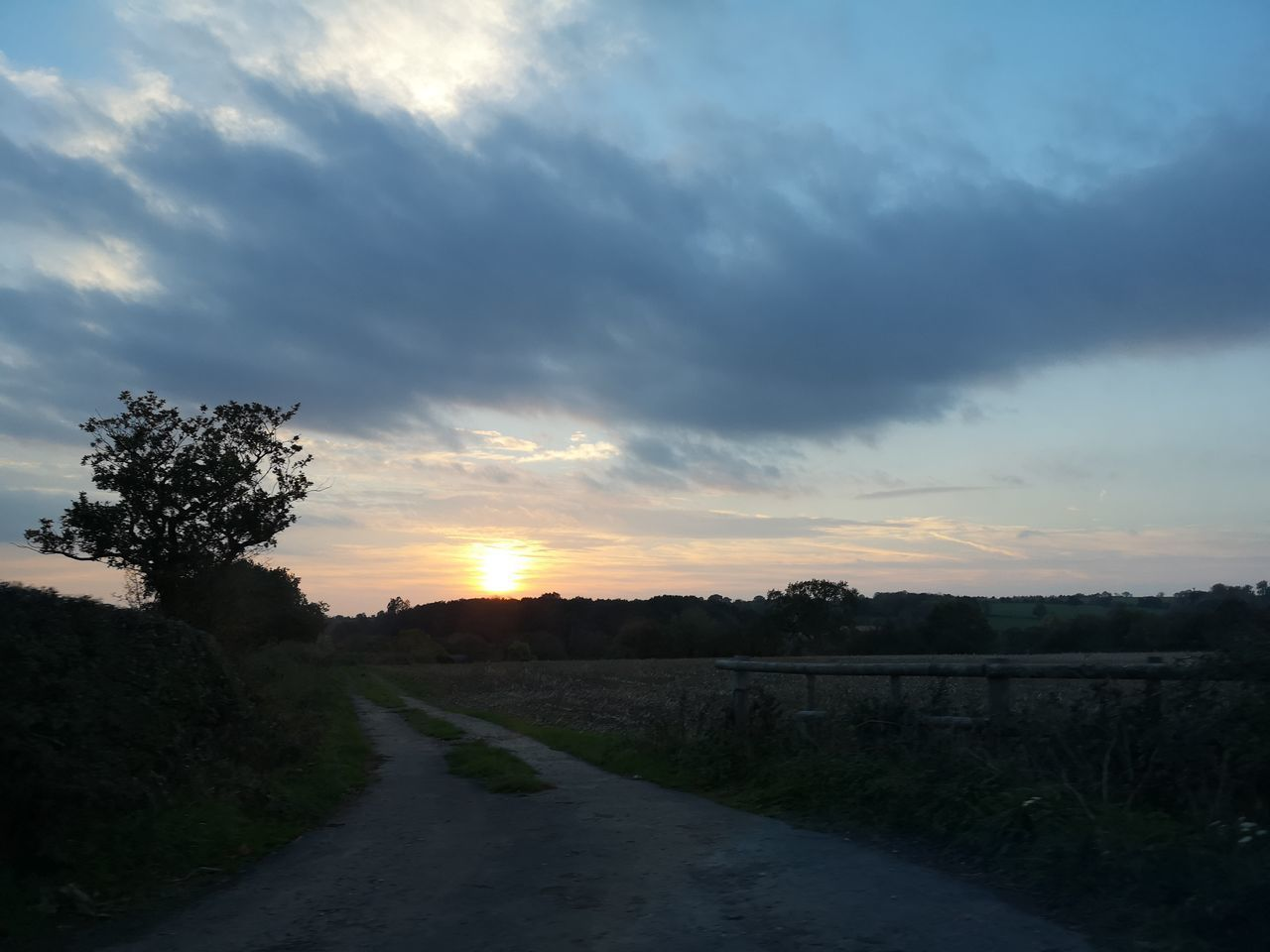ROAD BY FIELD AGAINST SKY AT SUNSET
