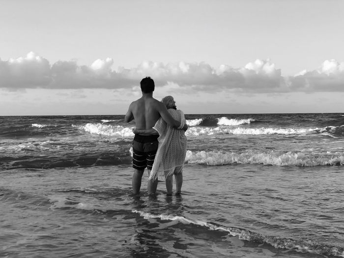 Rear view of friends standing in sea against sky